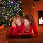 Mother and young daughter reading a book near a Christmas tree
